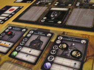 Dark Souls: The Card Game. Eine Aufnahme des Spielfeldes. Vier Spielfiguren stehen sich unterschiedlichen Gegnern gegenüber.
