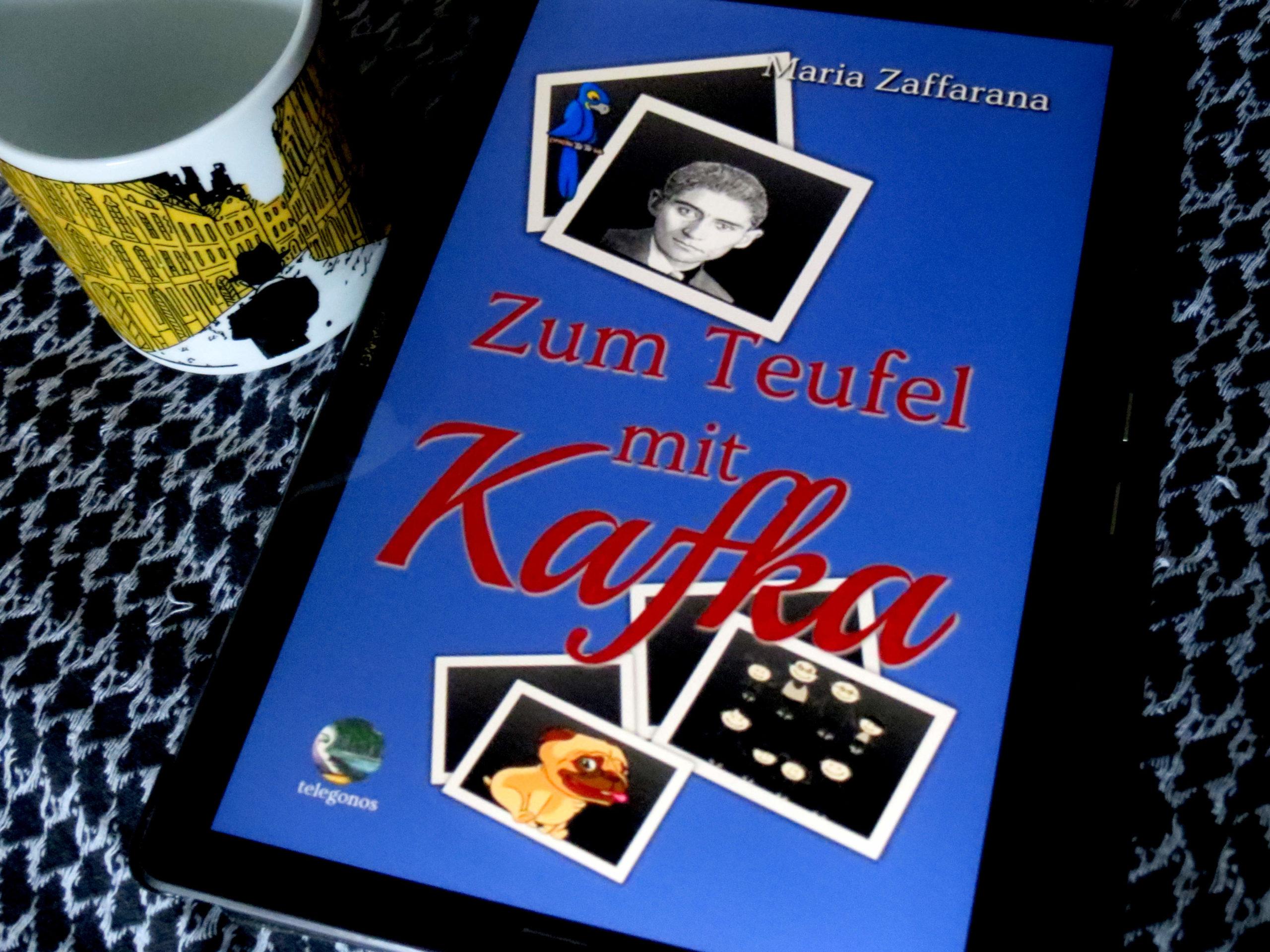 """E-Book """"Zum Teufel mit Kafka"""" von Maria Zaffarana, daneben eine Tasse mit der silhouette Franz Kafkas vor den gelben Fassaden Prags"""
