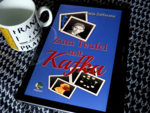 """E-Book """"Zum Teufel mit Kafka"""" von Maria Zaffarana, daneben eine Tasse mit der stark verblichenen Aufschrift """"Franz Kafka Praha"""""""